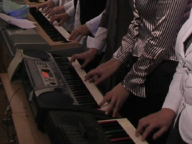 fingers of a long row of keyboard players