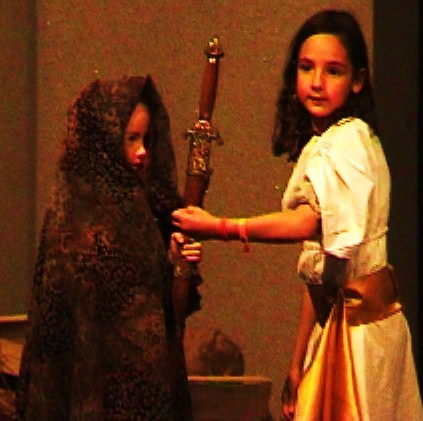 language-theatre little girl giving a sword to a beggar