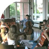 kids sitting in a circle playing cello
