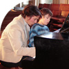 teacher and pupil playing piano together